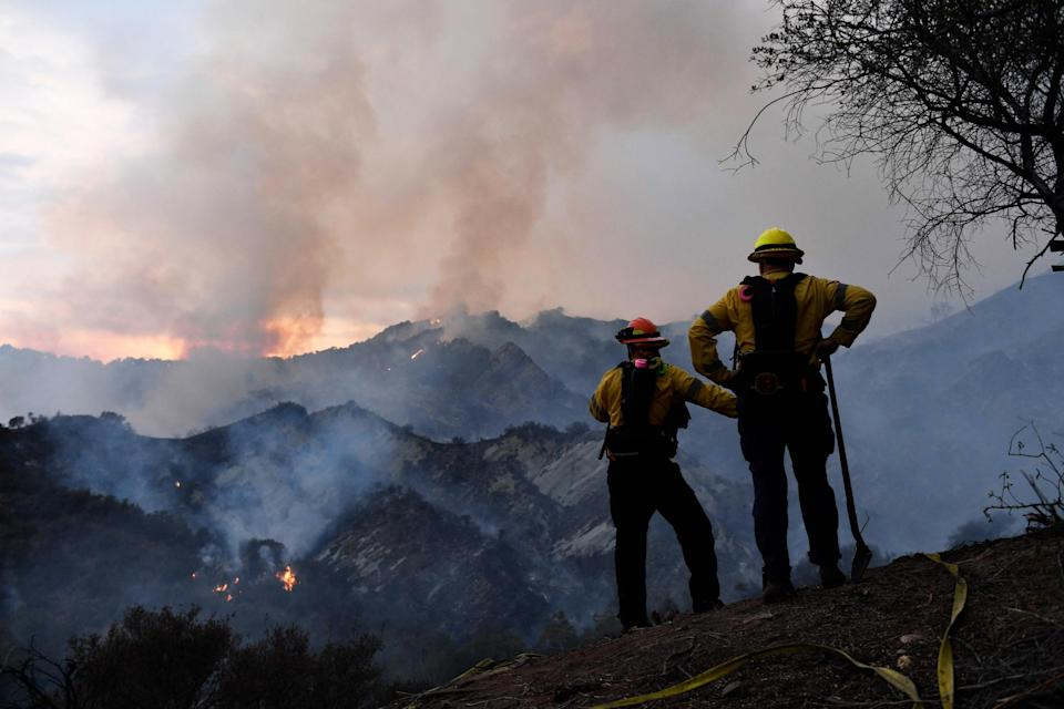 Firefighters work on a fire line as flames from the Palisades Fire glow in the distance in Topanga State Park, northwest of Los Angeles, on May 15, 2021. (Patrick T. Fallon / AFP - Getty Images)