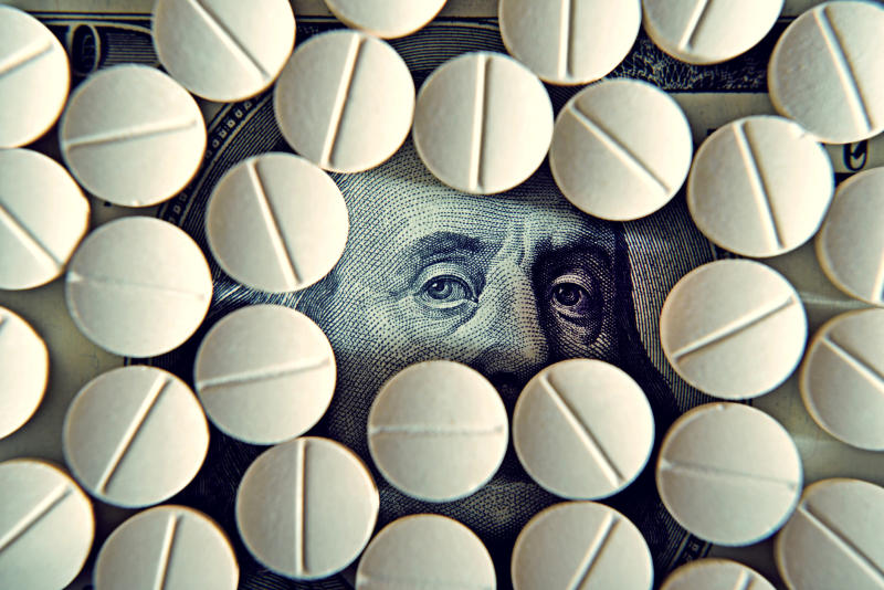 Prescription drug tablets covering a one-hundred-dollar bill, with Ben Franklin's eyes peering out between the pills.