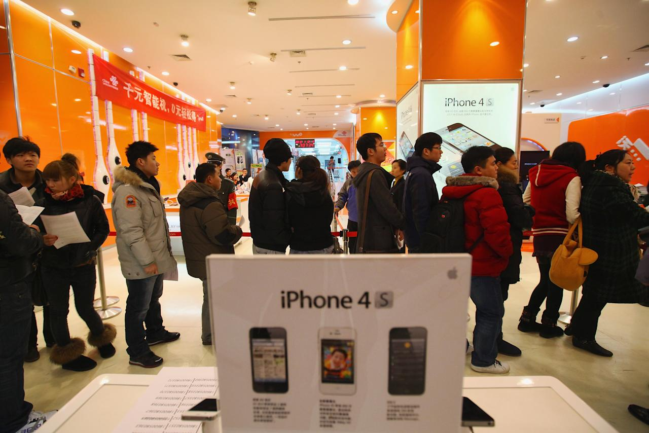 BEIJING, CHINA - JANUARY 13:  Chinese people line up to buy iPhone 4S in a China Unicom store in the early morning on January 13, 2012 in Beijing, China. Apple with China's leading telecommunications carrier, China Unicom, began to sell Apple's iPhone 4S at the Chinese mainland today.  (Photo by Feng Li/Getty Images)