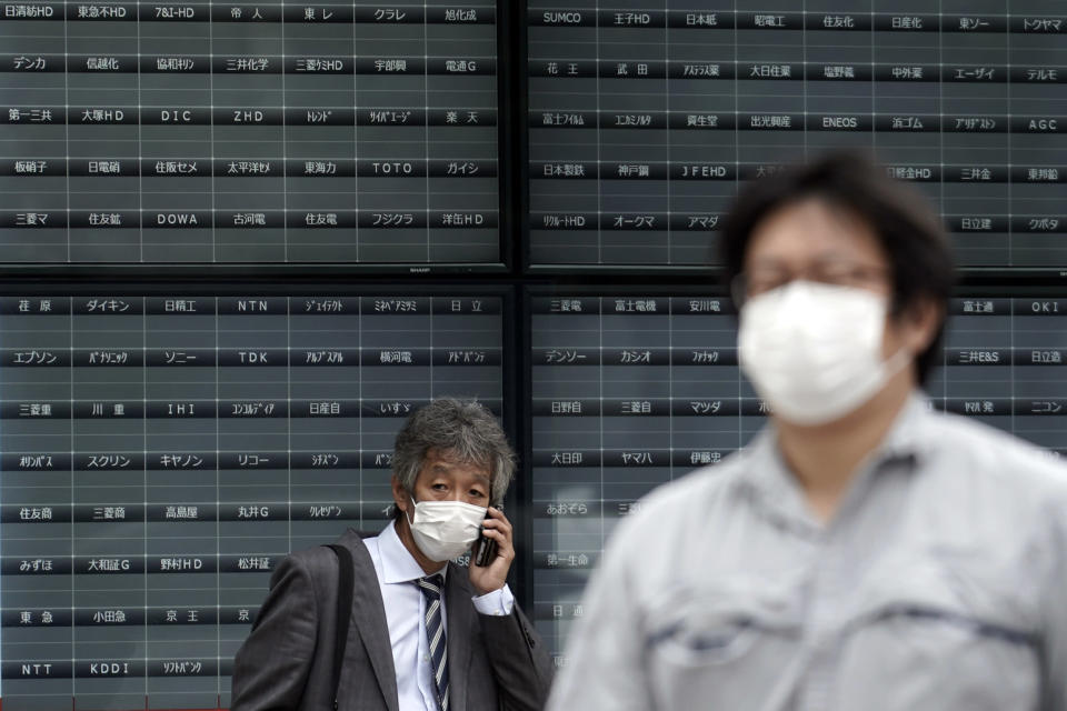 A man stands in front of a blank electronic stock board supposedly showing Japan's Nikkei 225 index at a securities firm in Tokyo Thursday, Oct. 1, 2020. Trading on the Tokyo Stock Exchange was suspended Thursday because of a problem in the system for relaying market information. Most other Asian markets were closed for national holidays. (AP Photo/Eugene Hoshiko)
