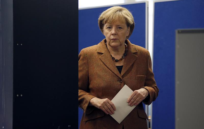 German Chancellor Angela Merkel, chairwoman of the Christian Democratic party CDU, leaves her voting booth before casting her vote in Berlin, Sunday, Sept. 22, 2013. 62 million voters in Germany are entitled to elect a new parliament as Merkel runs for her third term as chancellor. (AP Photo/Michael Sohn)