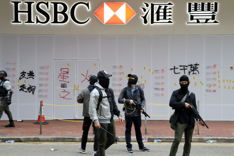 Armed undercover police officers guard a vandalized HSBC bank branch in Wan Chai during demonstrations on the New Year's Day in Hong Kong