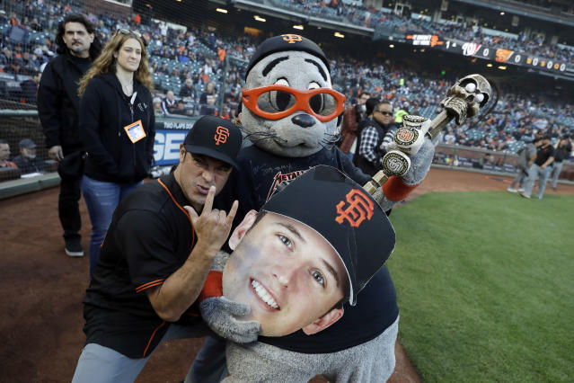 Metallica's Robert Trujillo poses for pictures with San Francisco Giants mascot Lou Seal during before a baseball game against the Washington Nationals Monday, April 23, 2018, in San Francisco. (AP Photo/Marcio Jose Sanchez)