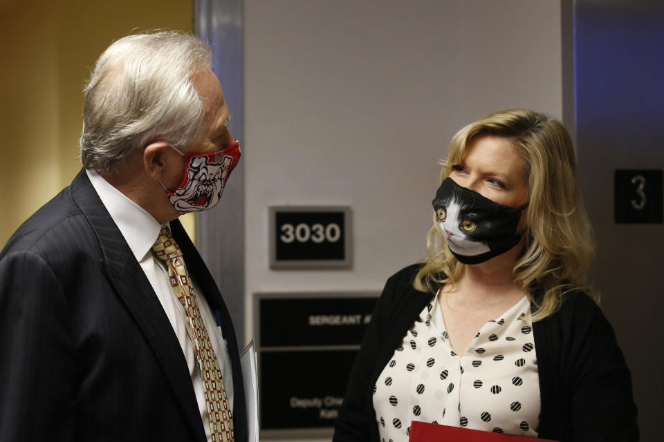 State Sen. Jim Nielsen, R-Gerber, left, wears a face mask representing his alma mater, the Bulldogs of Fresno State, as he talks with cat-fancier Sen. Cathleen Galgiani, D-Stockton, after the Senate session in Sacramento, Calif., Thursday, July 2, 2020. State lawmakers and those entering the Capitol are required to wear face masks and people often comply with their own personal tastes. (AP Photo/Rich Pedroncelli)