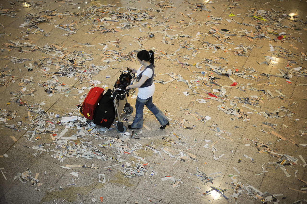 A passanger walks among rubbish and papers as Barcelona Airport cleaning staff protest against budget cuts at the El Prat International Airport on May 29, 2012 in Barcelona, Spain. Barcelona Airport cleaning staff are holding a two days strike portesting against the 1.3 million Euros budget cut that the airport operator company AENA has announced.  (Photo by David Ramos/Getty Images)