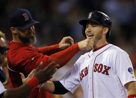 Boston Red Sox's David Ross (L) pulls on the beard of teammate Stephen Drew after Drew hit a two-run, home run against the Baltimore Orioles in the second inning of their MLB American League baseball game at Fenway Park in Boston, Massachusetts September 19, 2013. REUTERS/Brian Snyder