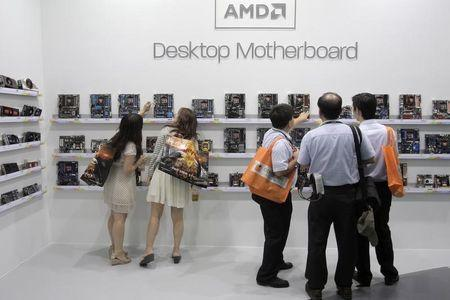 Visitors look at motherboards being displayed at the AMD booth during the 2012 Computex exhibition at the TWTC Nangang exhibition hall in Taipei