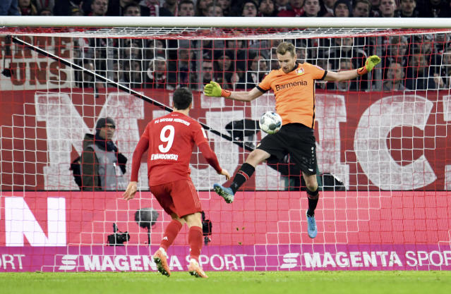 Leverkusen goalkeeper Lukas Hradecky, right, saves a shot from Bayern's Robert Lewandowski during their Bundesliga soccer match in Munich, Germany, Saturday, Nov. 31, 2019. Bayer Leverkusen keeper Lukas Hradecky dislodged a contact lens while playing against the German champions Bayern on Saturday, but he still helped Leverkusen to a surprise win. (Tobias Hase/dpa via AP)