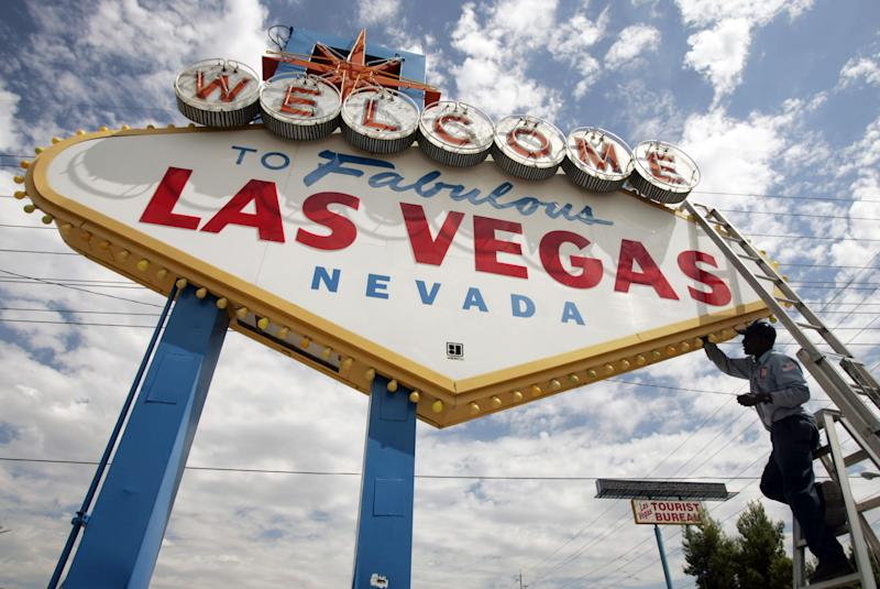 "FILE - This July 28, 2005 file photo shows an electric company worker changing ballasts and lamps on the ""Welcome to Las Vegas,"" sign in Las Vegas, Nev. Deals for round-trip airfare to Vegas along with inexpensive hotel packages are among the last-minute offers that travelers with flexible vacation schedules can find online, but the ability to book fast before the deals disappear is often key.  (AP Photo/Joe Cavaretta, file)"