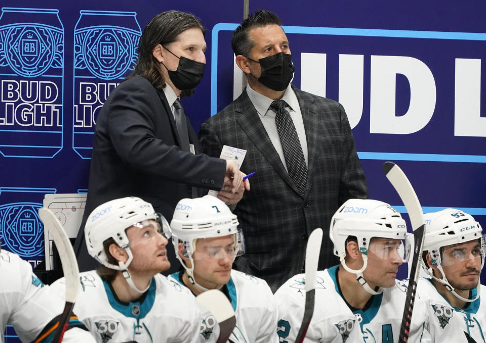 San Jose Sharks coach Bob Boughner, right, confers with assistant coach Mike Ricci during the second period of the team's NHL hockey game against the Colorado Avalanche on Tuesday, Jan. 26, 2021, in Denver. (AP Photo/David Zalubowski)