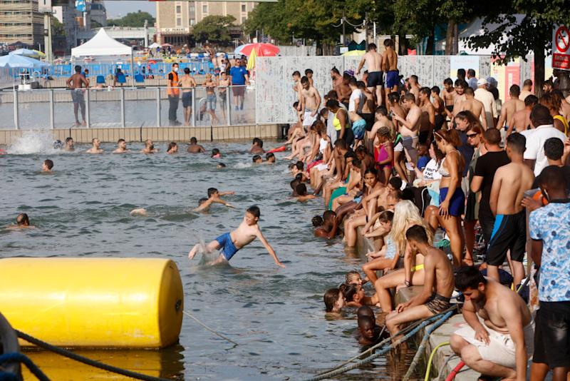 People dive into the water of the Canal de l'Ourq in Paris on Sunday (local time).