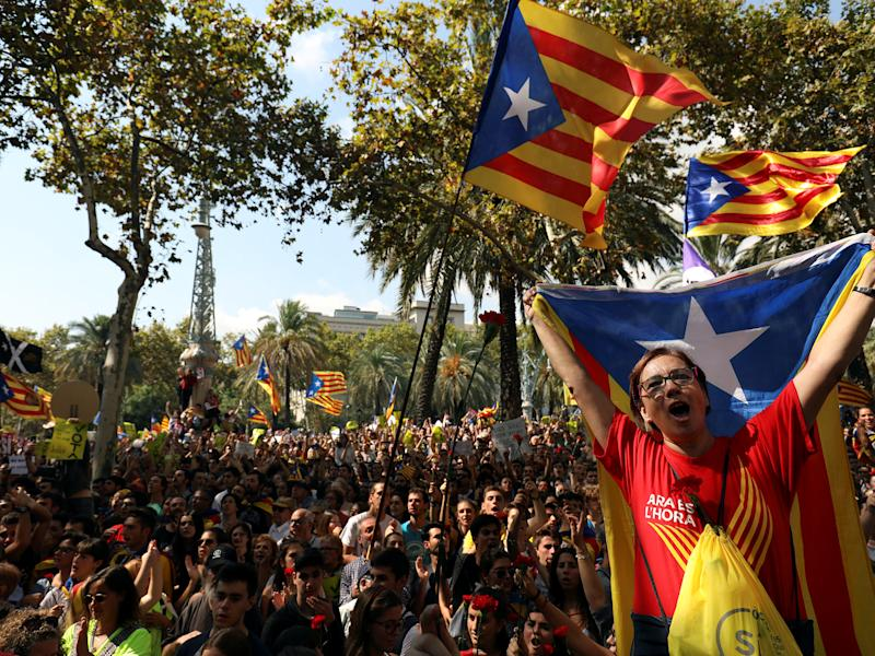 Protesters shout slogans and wave Esteladas (Catalan separatist flags) as they gather outside the High Court of Justice of Catalonia in Barcelona, Spain, on 21 September: Reuters