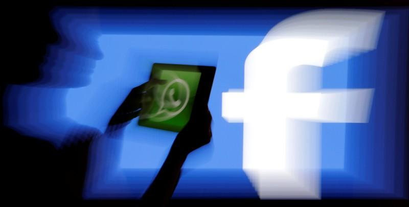 FILE PHOTO: Woman holds a tablet displaying WhatsApp's logo in front of the screen with the Facebook logo in this photo illustration taken in Prague