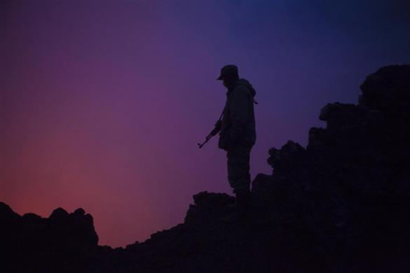 A Congolese soldier and guard for Virunga National Park is silhouetted by the glow from a lava lake boiling in the crater of Nyiragongo volcano near Goma in eastern Congo, August 30, 2010.