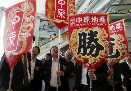 """Property sales agents from one of the biggest agent companies in Hong Kong carry banners with a Chinese character """"win"""", during the promotion of a property development in Hong Kong March 20, 2015. REUTERS/Bobby Yip"""