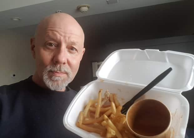 Kevin Rumsey of Whitehorse holds up some of the food he was provided at a hotel in Montreal that he's quarantining in. (Submitted by Kevin Rumsey - image credit)