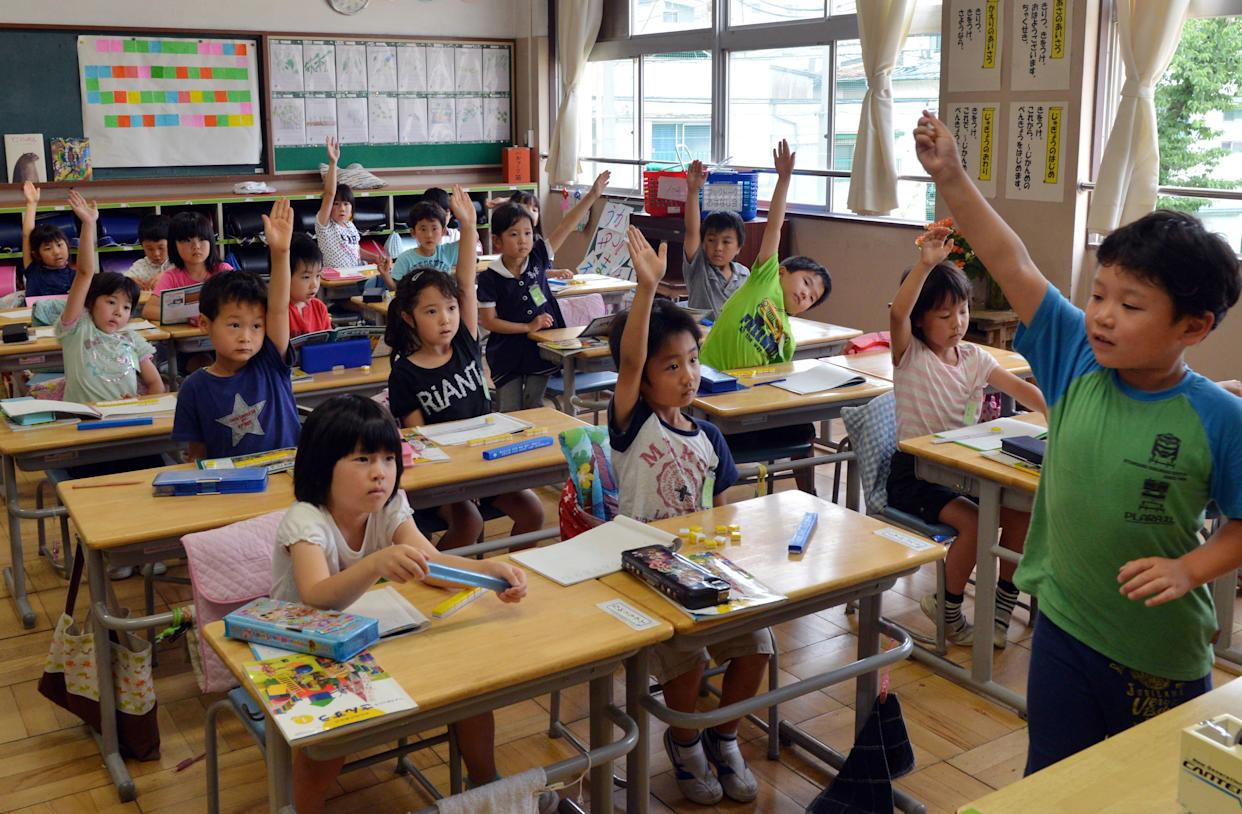 Six-year-old Japanese elemetary student Seishi Nishida raises his hand with classmates at school in Tokyo on June 11, 2013.