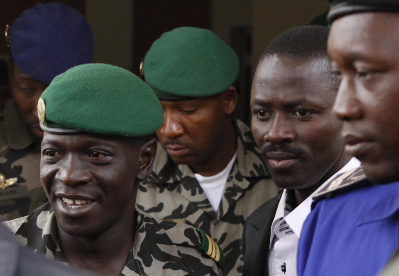 RETRANSMISSION FOR ALTERNATIVE CROP  Coup leader Capt. Amadou Haya Sanogo, left, leaves the airport in Bamako, Mali Thursday, March 29, 2012. Negotiations between Mali's military junta and four West African presidents seeking to restore the country's elected government will take place in Ivory Coast, after the plane carrying the heads of state to Mali turned around because demonstrators were on the airport tarmac, an adviser to Ivory Coast's president said Thursday.(AP Photo/Rebecca Blackwell)
