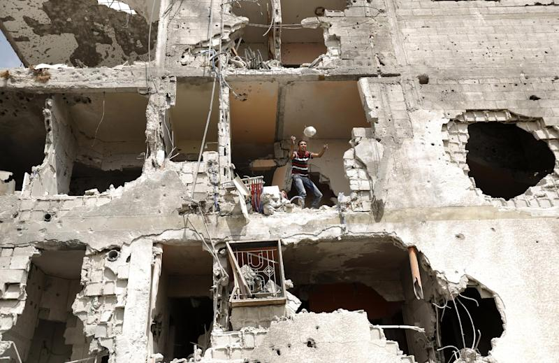 A Palestinian man throws an item from a destroyed house in the Al-Shejaea neighbourhood of Gaza City on August 5, 2014 (AFP Photo/Mohammed Abed)