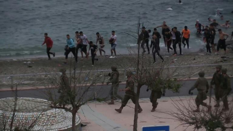 Spanish security forces try to push back migrants arriving into Ceuta by sea