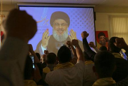 FILE PHOTO: Lebanon's Hezbollah leader Sayyed Hassan Nasrallah addresses his supporters from a screen during a rally to commemorate Hezbollah Wounded Veterans Day in Beirut's southern suburbs