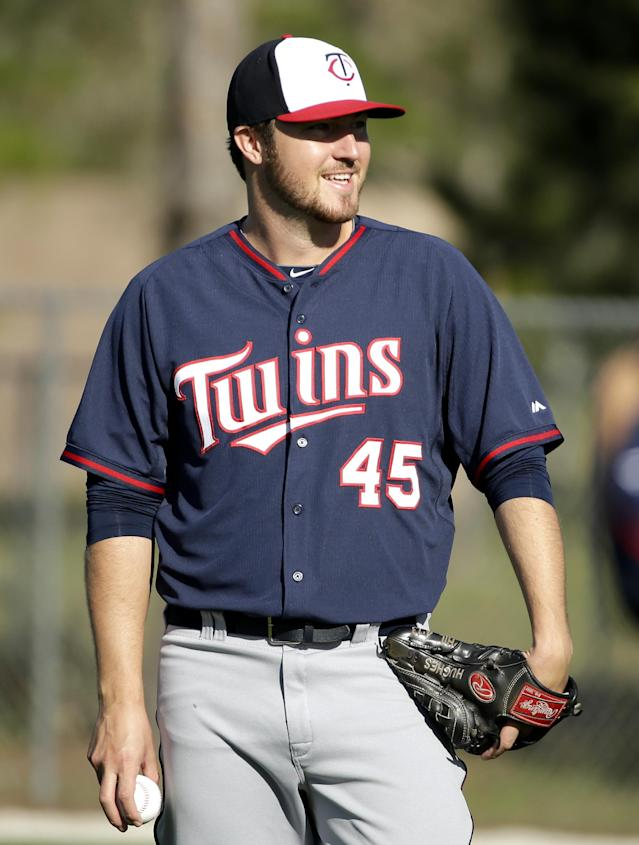 Minnesota Twins pitcher Phil Hughes talks while warming up on the field during spring training baseball practice Thursday, Feb. 20, 2014, in Fort Myers, Fla. (AP Photo/Steven Senne)