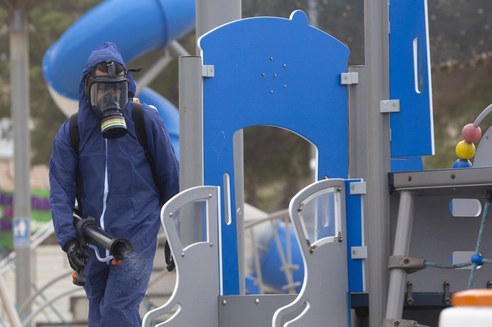 A worker sprays disinfectant as a precaution against the coronavirus in a playground in the central Israeli city of Bat Yam, Wednesday, March 18, 2020. Israel braced for its first fatalities as the number of coronavirus cases spiked by 25% on Wednesday. For most people, the virus causes only mild or moderate symptoms. For some it can cause more severe illness. (AP Photo/Sebastian Scheiner)