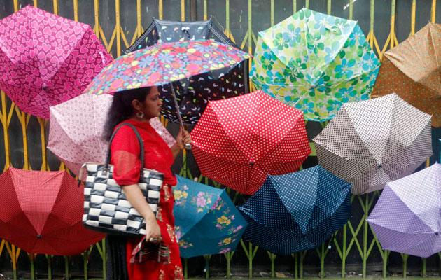 A woman holding an umbrella walks past rows of umbrellas displayed for sale along a busy street as it drizzles in Kolkata July 6, 2012. The June-September monsoon rains, the main source of water for 55 percent of India's arable land, were 30 percent lower-than-normal since the beginning of the monsoon season. REUTERS/Rupak De Chowdhuri