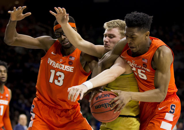 Syracuse's Paschal Chukwu (13) and Tyus Battle (25) compete for a loose ball with Notre Dame's Dane Goodwin during the second half of an NCAA college basketball game Saturday, Jan. 5, 2019, in South Bend, Ind. Syracuse won 72-62. (AP Photo/Robert Franklin)
