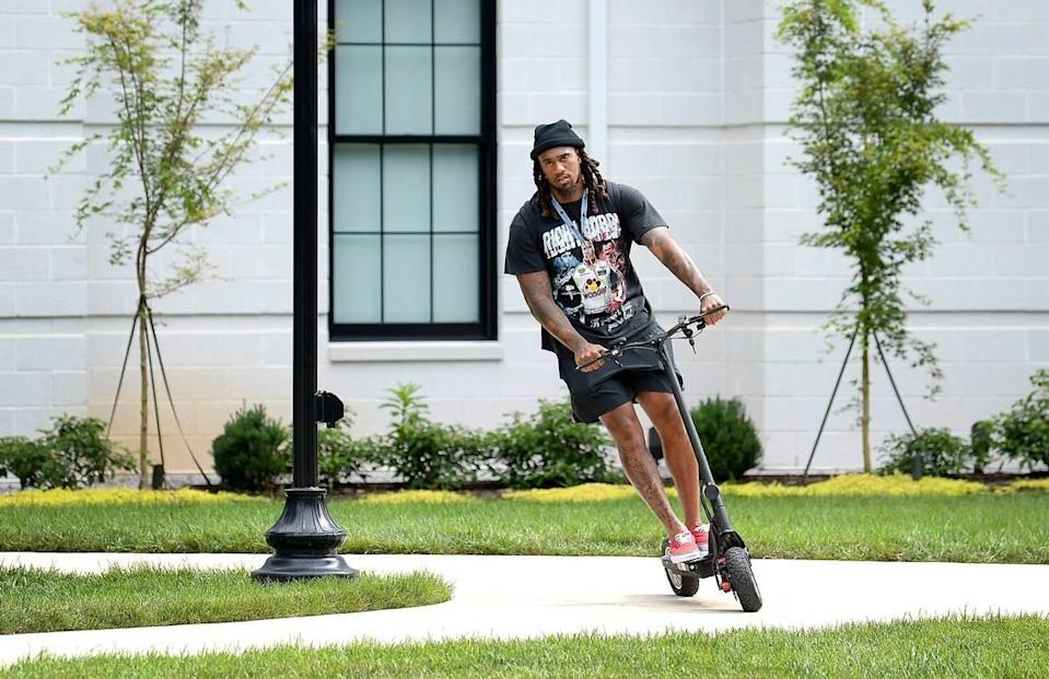 """Carolina Panthers linebacker Shaq Thompson rides a scooter outside the team's dormitory at Wofford College in Spartanburg Tuesday. Thompson said with all the young players on defense that, at age 27, he felt like a """"2015 Honda."""""""