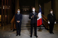 French President Emmanuel Macron, center, delivers a speech while Interior Minister Gerald Darmanin, left, and Seine-Saint-Denis prefect Georges-Francois Leclerc listen, after a visit on the fight against separatism at the Seine Saint Denis prefecture headquarters in Bobigny, a northeastern suburbs of Paris, Tuesday Oct. 20, 2020. Authorities were looking into about 50 associations suspected of encouraging hate speech and the issue will be discussed at a Cabinet meeting Wednesday after the history teacher Samuel Paty was beheaded on Friday by an 18-year-old Moscow-born Chechen refugee. (Ludovic Marin, Pool via AP)