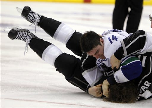 Vancouver Canucks right wing Alex Burrows (14) pins Los Angeles Kings center Anze Kopitar of Yugoslavia to end a fight during the second period of Game 3 in a first-round NHL Stanley Cup playoff series in Los Angeles, Sunday, April 15, 2012. (AP Photo/Alex Gallardo)