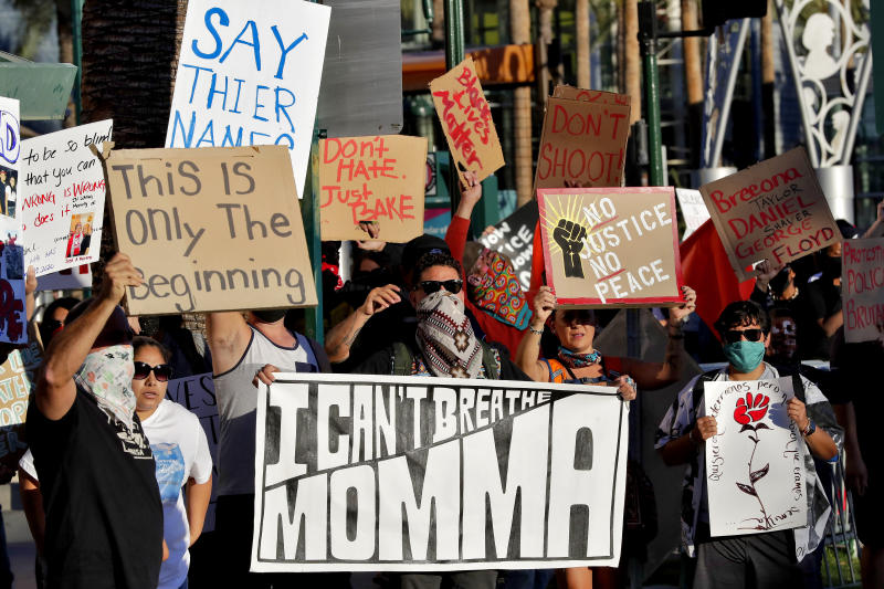 Protesters rally Tuesday, June 9, 2020, in Mesa, Ariz. demanding police reform. The protest was prompted by the death of George Floyd, a black man who died after being restrained by Minneapolis police officers May 25. (AP Photo/Matt York)