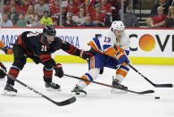 Carolina Hurricanes' Sebastian Aho (20), of Finland, chases New York Islanders' Mathew Barzal (13) during the first period of Game 4 of an NHL hockey second-round playoff series in Raleigh, N.C., Friday, May 3, 2019. (AP Photo/Gerry Broome)