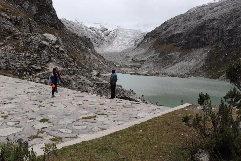 people standing on a dam overlooking a glacial lake