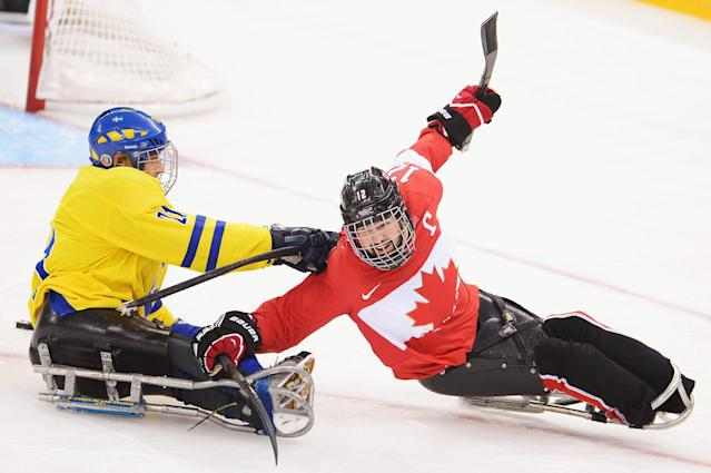 SOCHI, RUSSIA - MARCH 08: Greg Westlake of Canada is challenged by Marcus Holm of Sweden during the Preliminary Round Group A match between Canada and Sweden at Shayba Arena on March 8, 2014 in Sochi, Russia. (Photo by Dennis Grombkowski/Getty Images)