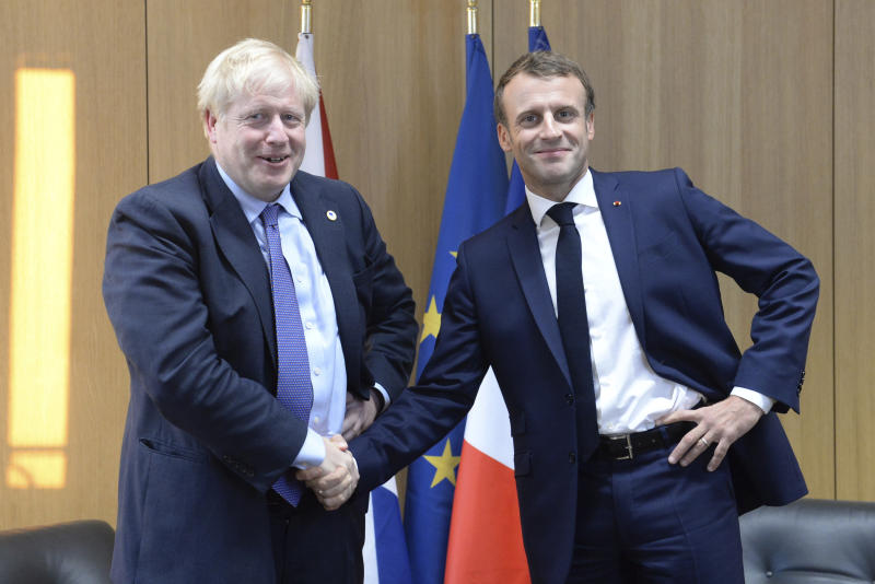 Britain's Prime Minister Boris Johnson poses as he shakes the hand of French President Emmanuel Macron, right, during a European Union leaders summit in Brussels, Belgium, Thursday Oct. 17, 2019.  Britain and the European Union reached a new tentative Brexit deal on Thursday, hoping to finally escape the acrimony, divisions and frustration of their three-year negotiation. (Johanna Geron/Pool via AP)
