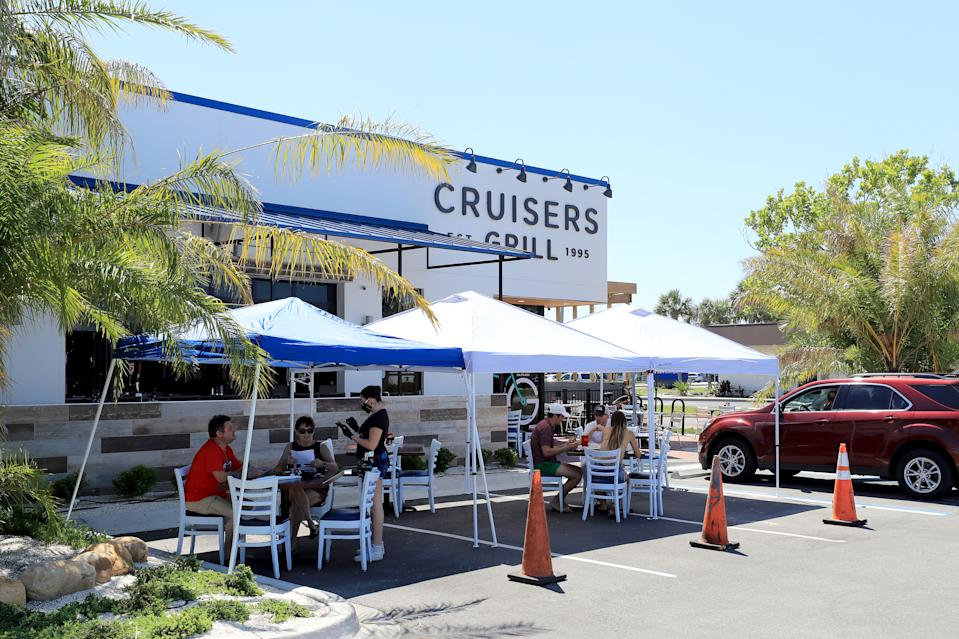 JACKSONVILLE BEACH, FLORIDA - MAY 04: People are seen dining outside at Cruisers Grill as the state of Florida enters phase one of the plan to reopen the state on May 04, 2020 in Jacksonville Beach, Florida. Restaurants, retailers, beaches and some state parks reopen today with caveats, as the state continues to ease restrictions put in place to contain the coronavirus (COVID-19). (Photo by Sam Greenwood/Getty Images)