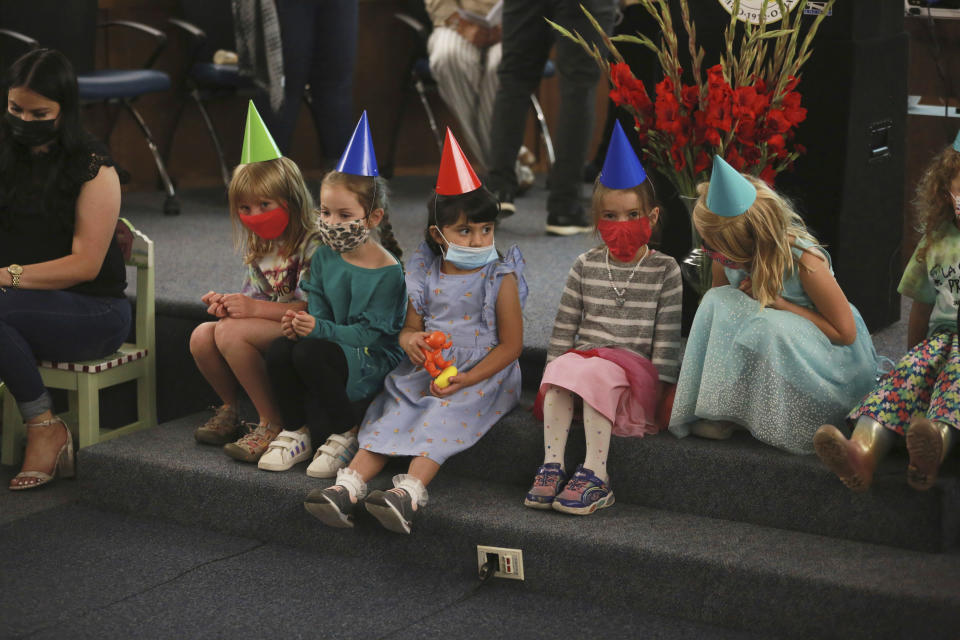 Children wait for Gov. Michelle Lujan Grisham to make an announcement about child care subsidies on Thursday, July 1, 2021, in Santa Fe, N.M. New Mexico is expanding child care subsidy eligibility to the middle class by tapping into pandemic relief funds. (AP Photo/Cedar Attanasio)