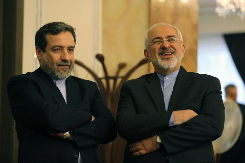 Iran's chief nuclear negotiator Abbas Araghchi (L) and Foreign Minister Javad Zarif listen to President Hassan Rouhani (unseen) speaking during a press conference in Tehran on April 3, 2015