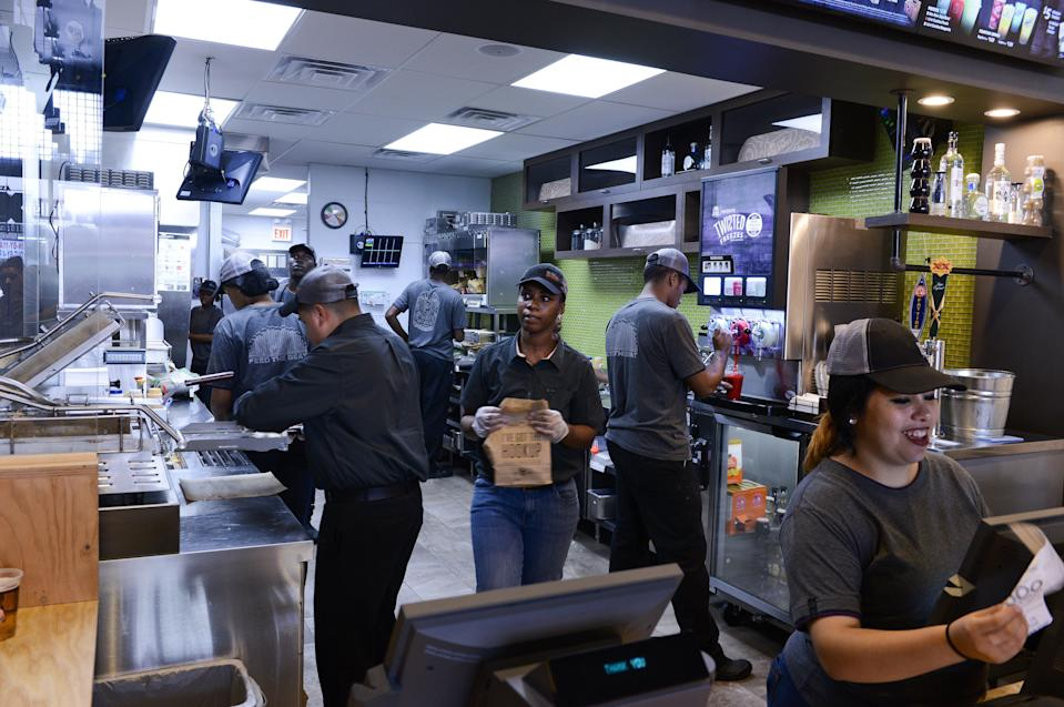 Employees prepare food at a Taco Bell Cantina restaurant on Sept. 22, 2015, in Chicago.