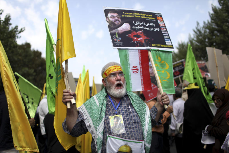 An Iranian man chants slogans as he holds an anti-Israeli placard with a portrait and quotation of Lebanese Hezbollah leader Sheik Hassan Nasrallah during an annual pro-Palestinian rally marking Al-Quds (Jerusalem) Day in Tehran, Iran, Friday, Aug. 2, 2013. The last Friday of the Islamic holy month of Ramadan is observed in many Muslim countries as Al-Quds day, as a way of expressing support to the Palestinians and emphasizing the importance of Jerusalem to Muslims. (AP Photo/Ebrahim Noroozi)
