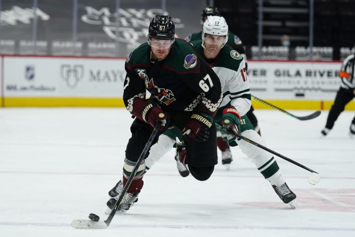 Arizona Coyotes left wing Lawson Crouse (67) shields Minnesota Wild left wing Marcus Foligno from the puck during the second period of an NHL hockey game Friday, March 5, 2021, in Glendale, Ariz. (AP Photo/Rick Scuteri)