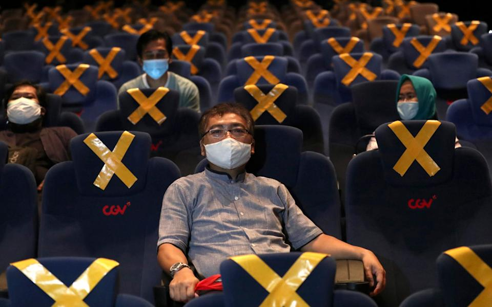 People sit spaced apart amid physical distancing markers as they wait for the start of a movie  - AP Photo/Tatan Syuflana