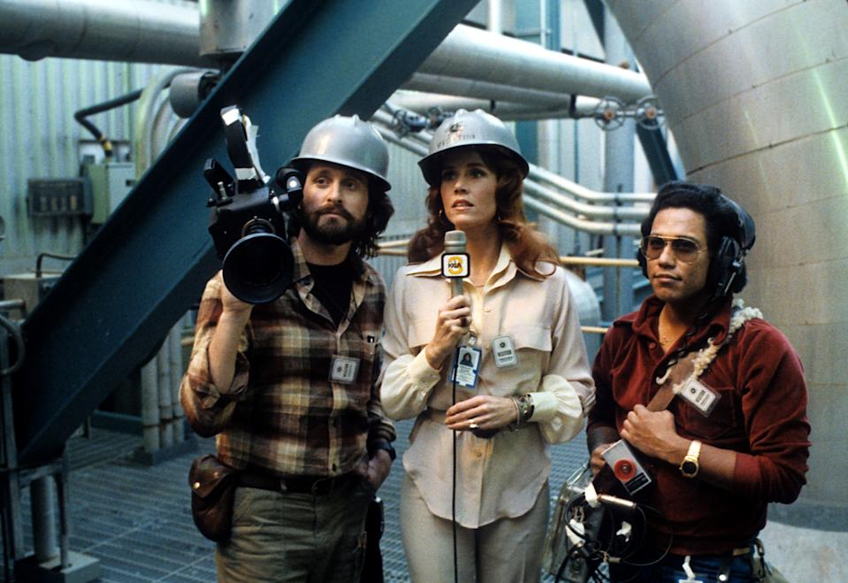 Jane Fonda with a microphone in her hand and Michael Douglas holding a movie camera on his shoulder in a scene from the film 'The China Syndrome', 1979. (Photo by Columbia Pictures/Getty Images)