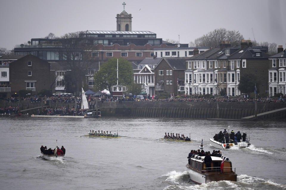 Watched by thousands of spectators from the river banks, as Cambridge boat, centre left, lead the Oxford boat, centre right, during The Boat Race on the River Thames in London, Sunday April 7, 2019.  The 165the annual Boat Race traditionally fought out between Oxford and Cambridge university rowing crews. (Adam Davy/PA via AP)