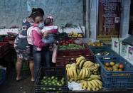 A woman carrying a baby buys fruit at a shop amid the new coronavirus pandemic in Rio de Janeiro, Brazil, Friday, Oct. 9, 2020. Many people in Brazil are struggling to cope with less pandemic aid from the government and jumping food prices, with millions expected to slip back into poverty. (AP Photo/Silvia Izquierdo)