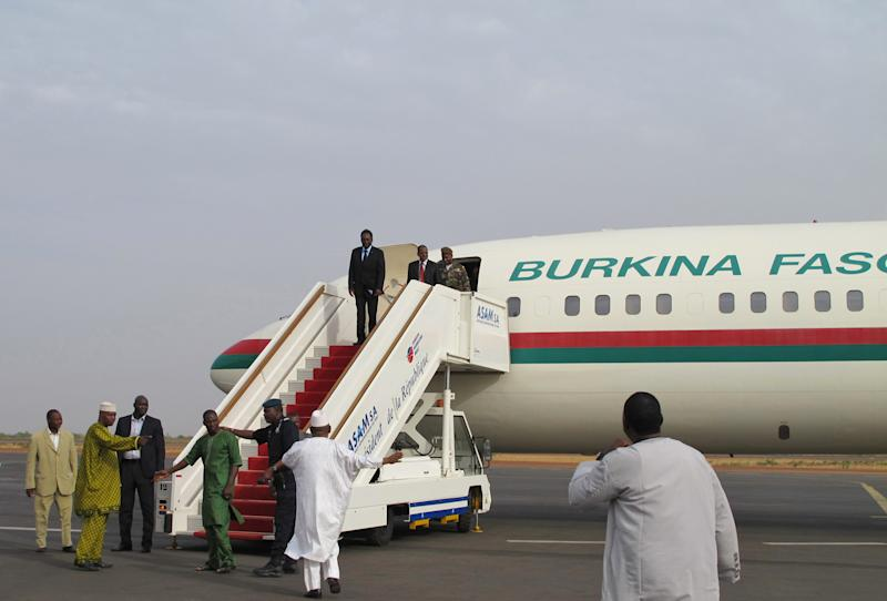Dioncounda Traore, Mali's parliamentary head who was forced into exile after last month's coup, stands at the top of the airplane steps as he disembarks on arrival at the airport to take up his constitutionally-mandated post as interim president, in Bamako, Mali Saturday, April 7, 2012. Traore's return comes after coup leader Capt. Amadou Haya Sanogo signed an accord late Friday, agreeing to return the nation to constitutional rule.(AP Photo/Rukmini Callimachi)