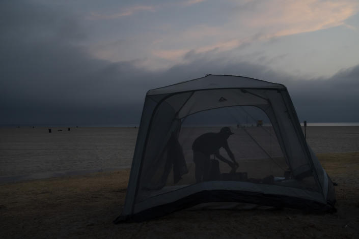 Marc Dilk, a 32-year-old homeless man, tidies up around his tent on the beach in the Venice neighborhood of Los Angeles, Tuesday, June 29, 2021. (AP Photo/Jae C. Hong)