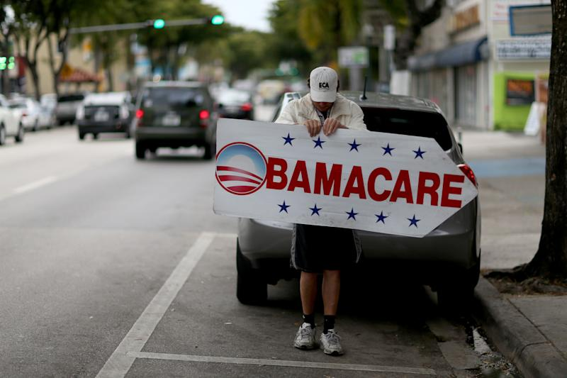 Pedro Rojas holds a sign directing people to an insurance company where they can sign up for the Affordable Care Act. (Photo by Joe Raedle/Getty Images)